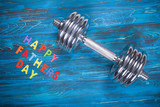 Happy Father's Day inscription with dumbbell on wooden blue background