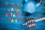 Happy Father's Day inscription with kettlebell and dumbbell on blue wooden table
