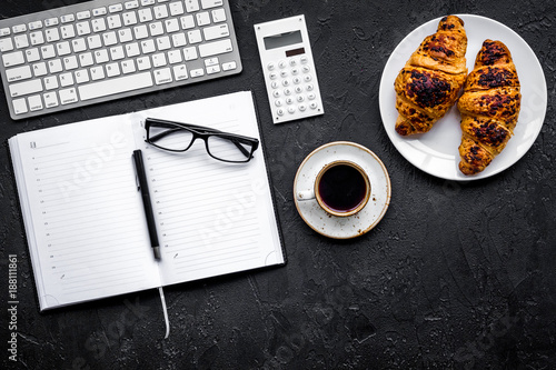 Sticker Morning of businessman. Coffee and croissants for breakfast near keyboard and notebook. Black background top view copy space