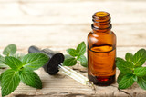 Peppermint essential oil and leaves on the wooden board - 188113092
