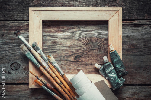 Foto Murales Wooden stretcher bar, paintbrushes, roll of artist canvas and paint tubes on old wooden background. Top view. Copy space for text.