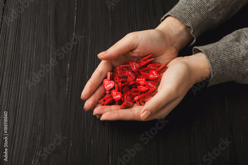 Foto Murales Valentine day background, clothespins and heart in female hands