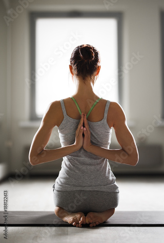 Obraz na płótnie Relaxed young sportswoman doing yoga and meditating in studio
