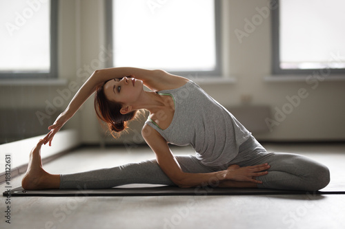 Fototapeta Young sporty woman doing yoga stretching exercise sitting in gym near bright windows