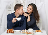 happy couple drinking coffee and talking near window with a street view - travel and love concept
