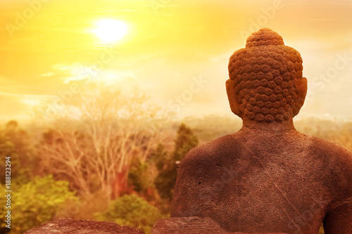Canvas Boeddha A statue of Buddha against the background of the sunrise in the temple of Borobodur. Java island. Indonesia. Famous historical place. Outside.