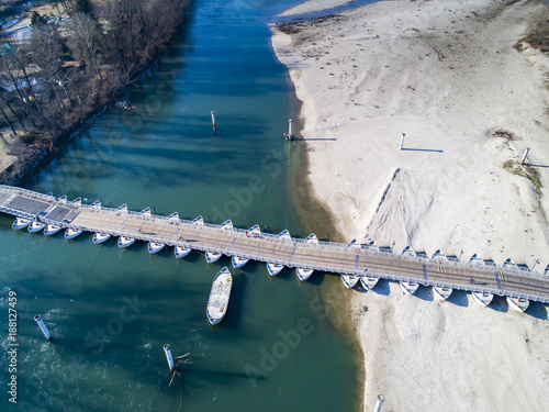 Bridge of boats on the Ticino river, near Bereguardo town, Lombardy, Italy. Aerial view. This pontoon bridge uses floats or shallow-draft boats to support a deck for pedestrian and vehicle travel. - 188127459