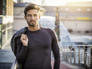 One handsome young man in urban setting in European city, standing