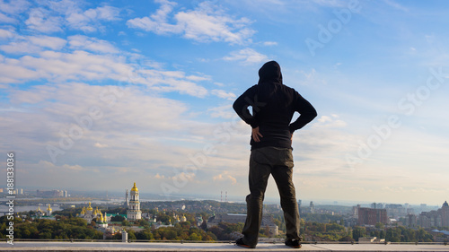 Fotobehang Kiev man stands on the edge of the roof of a tall building
