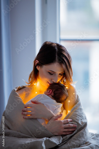 Mother and infant wrapped in blanket on bed.
