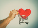 Male hands holding shopping cart with heart. - 188139835