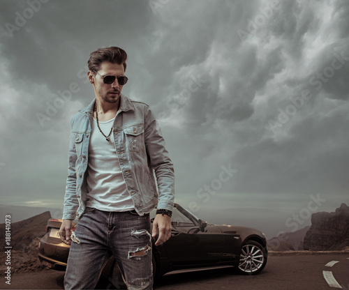 Fotobehang Konrad B. Handsome man posing next to the luxurious convertible car