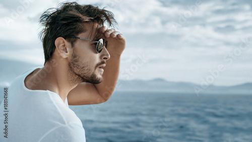 Foto Spatwand Konrad B. Portrait of a handsome man watching ocean waves