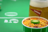 closeup of a small bowl of chili and beer mug on table decorated for superbowl party - 188147425