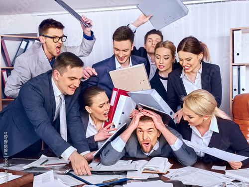 Business people office. Team people are unhappy with their leader. Intern man manager does not cope with his duties. Crowd in stress throw up their chief's papers. One staff member took out all.