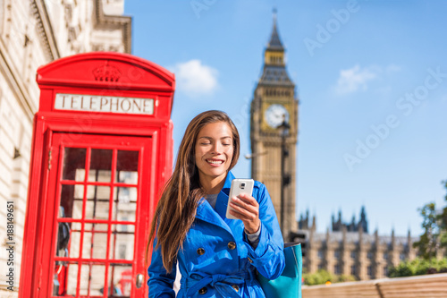 London mobile phone business Asian woman writing text message using cellphone at red telephone booth by the Big Ben Clock Tower, London, England, UK. Europe travel destination.