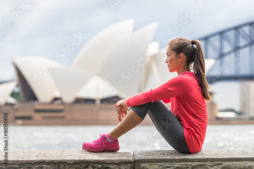 Foto op Canvas Sydney Sydney city woman living an active lifestyle relaxing at urban park after running cardio exercise outside in summer. Asian girl sitting with Sydney tourist attraction in background.