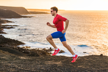 Trail runner sport fitness man ultra running on ocean cliff in sunset. Sports athlete jogging training outdoors in rocky landscape by the sea. Active lifestyle compression clothes.