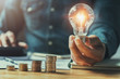 Leinwandbild Motiv business man hand holding lightbulb with using calculator to calculate and money stack. idea saving energy and accounting finance in office concept