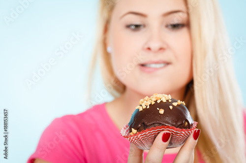 Foto Murales Woman holding chocolate cupcake about to bite