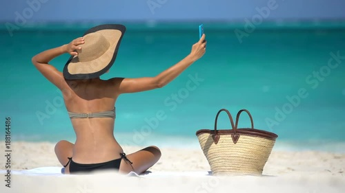 Stylish woman taking selfie on beach. Summer travel holidays concept while sunbathing on beach. Woman in bikini is photographing using smart phone on vacation.