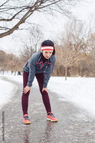 Portrait of Caucasian young woman taking a break after  jogging outside in winter park. Girl resting after running outdoors wearing sportswear, headband and headphones.