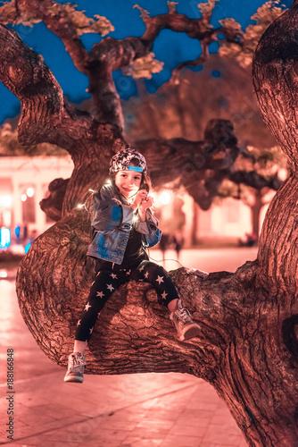 Foto Murales preschool girl sitting on a tree branch