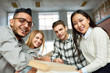 Multi-ethnic group of cheerful students looking at camera and smiling sitting at desk in lecture hall of modern college