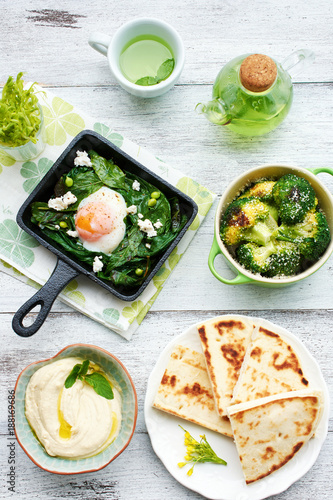 Foto Murales Poached egg with spinach, basil and feta in a pan, baked broccoli, hummus, flatbread and green tea on white table. Healthy oriental style breakfast or dinner.