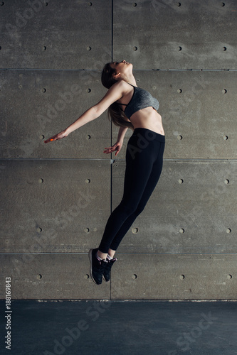 Poster Sports young woman doing back bend jump