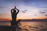 yoga on sup board, silhouette of woman on the beach - 188170416
