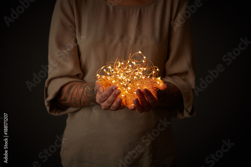 Christmas lights garland in female hands