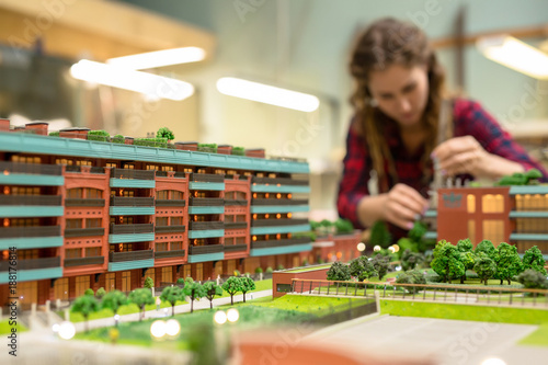 Female professional working over layout design of the city with new buildings