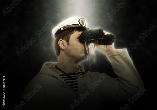 Fototapeta Man in captain hat looks on binocular
