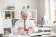 Happy senior businessman in birthday-cap untying ribbon on top of gift-box in office