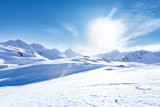 Junge sportliche Frau fährt Ski, macht Winter Sport in einem Winter Paradis. Schnee bedeckte Berge, blauer Himmel und Farbenfroher Ski Anzug