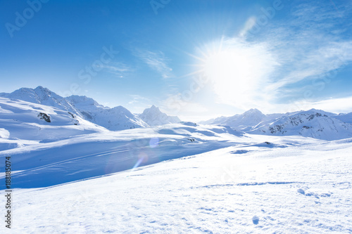 Leinwanddruck Bild Junge sportliche Frau fährt Ski, macht Winter Sport in einem Winter Paradis. Schnee bedeckte Berge, blauer Himmel und Farbenfroher Ski Anzug