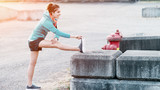 Young sporty woman listening music and doing stretching in city urban area - 188186409