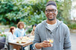 African guy with refreshing drink looking at camera with friends having dinner on background