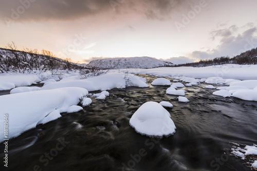 Aluminium Blauwe hemel Water stream with rocks in a winter landscape in twilight.