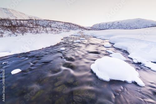 Foto Murales Water stream with rocks in a winter landscape in twilight.