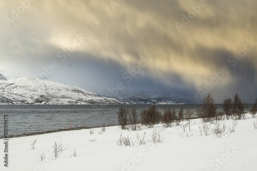 Foto Murales Sunset at the lakeside with rocks of a fjord during a snow storm in a snowy winter landscape.