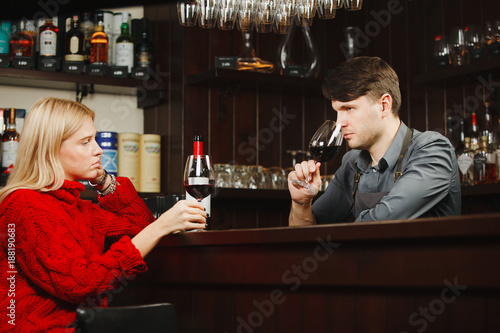 Foto Murales Bartender and girl-visitor smell wine aroma from glasses