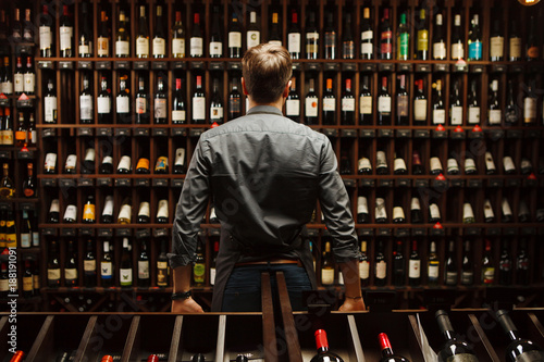Bartender at wine cellar full of bottles with exquisite drinks - 188191091