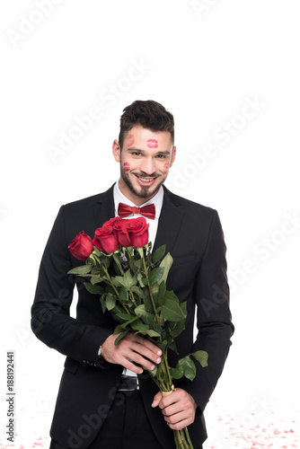 man with lips traces on face holding bouquet of roses isolated on white, valentines day concept