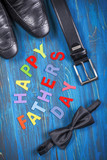 Composition for Father's day with belt, shoes and bow tie on wooden background