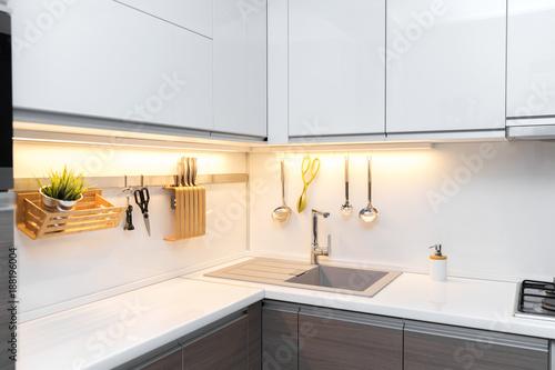 white gloss kitchen interior with worktop lighting