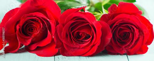 Świeże czerwone róże na seledynowym stole