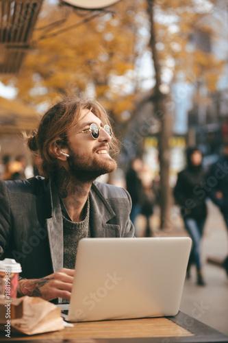 Foto Murales Portrait of a smiling bearded man in earphones