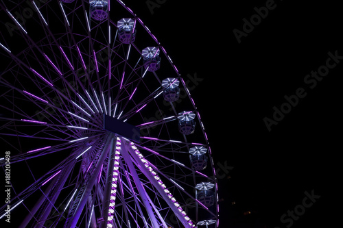 Staande foto Amusementspark Violet ferris wheel illuminated at night